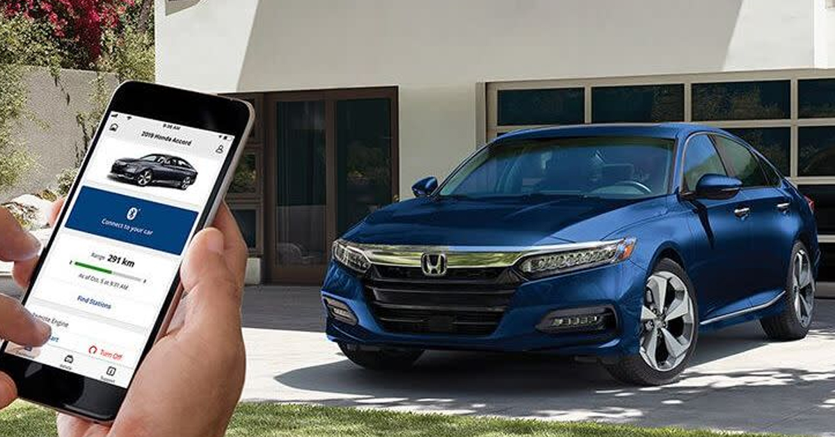 Honda driver walking next to a new Honda from South Motors Honda using the Hondalink app.